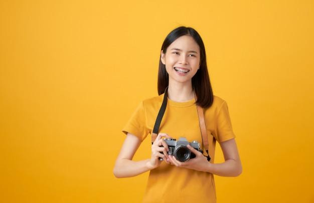 Young smiling asian woman tourist holding camera and looking to ...