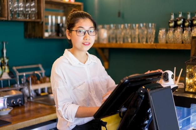 Smiling asian cashier working in cafe and looking at camera ...