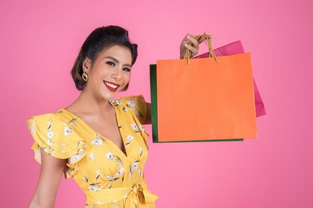 Beautiful asian woman holding colored shopping bags | Free Photo
